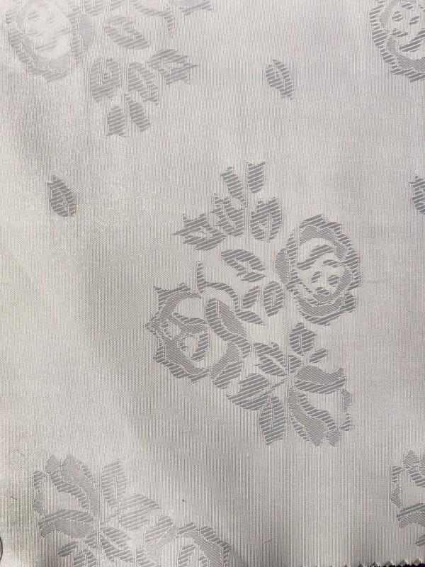 Zdjęcie przedstawia art. AZ, inaczej zwany jako ŻAKARD (100% poliester, gramatura 100 g/m2, szerokość 160 cm) w kolorze białym, we wzorze (AZ01 Rose, kol. 0001) widocznym na zdjęciu.