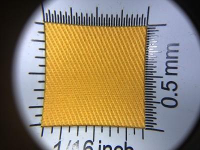 Zdjęcie przedstawia art. 1105U, elanobawełna (80% poliester, 20% poliester, gramatura 240 g/m2, szerokość 150 cm) w kolorze żółtym (nr. 1820) w przybliżeniu, pod lupą, ukazanie struktury tkaniny.