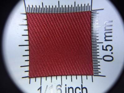 Zdjęcie przedstawia art. 1124EU, elanobawełna (65% poliester, 35% poliester, gramatura 210 g/m2, szerokość 150 cm) w kolorze czerwonym (nr. 3017) w przybliżeniu, pod lupą, ukazanie struktury tkaniny.