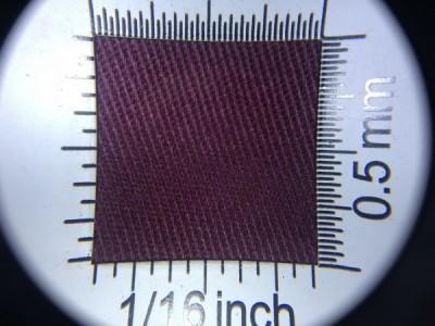Zdjęcie przedstawia art. 1124EU, elanobawełna (65% poliester, 35% poliester, gramatura 210 g/m2, szerokość 150 cm) w kolorze bordowym (nr. 3745) w przybliżeniu, pod lupą, ukazanie struktury tkaniny.