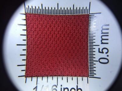 Zdjęcie przedstawia art. PLV6, która na rynku znana jest jako dzianina sportowa, (100% poliester, gramatura 130 g/m2, szerokość 150 cm) w kolorze czerwonym (nr. 3765) w przybliżeniu, pod lupą.